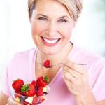 A senior woman enjoys food good for her teeth.