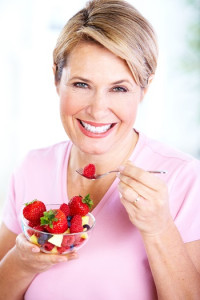 A senior woman enjoys food good for her teeth.