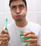 A man uses mouthwash after brushing his teeth.
